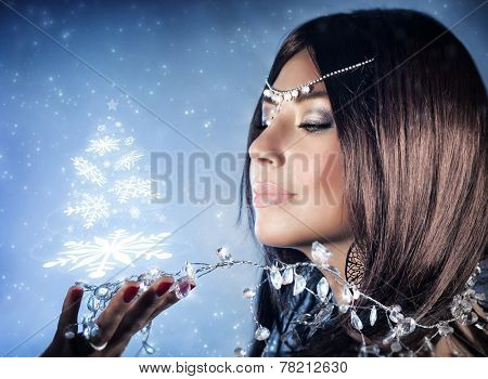 Closeup portrait of beautiful snow queen with crown on head holding on hand magical glowing Christmas tree, winter fashion and makeup