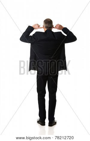 Full length back view businessman plugging his ears.