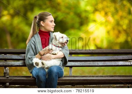 young woman hugging a maltese dog out in the park