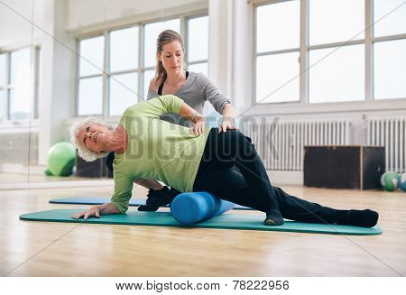 Instructor Helping Senior Woman For A Myofascial Release Techniq