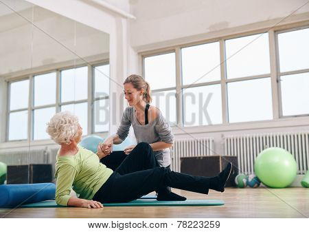 Female Trainer Helping Old Woman Getting Up At Gym