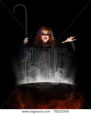 Young witch with cauldron isolated