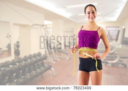 Young sporty girl with centimeter tape at gym club