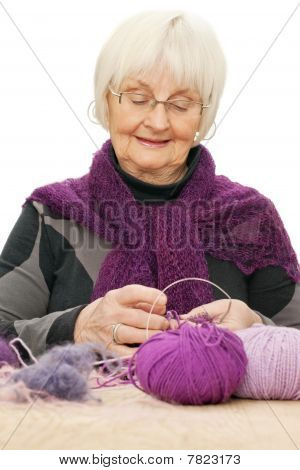 Portrait Of Active Old Woman Knitting Against White Background