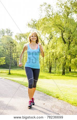 Smiling woman exercising on running path in green summer park
