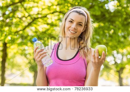 Fit blonde holding water and apple on a sunny day