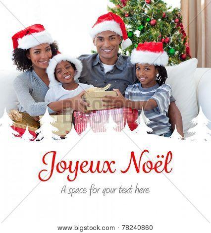 Smiling family sharing Christmas presents against joyeux noel