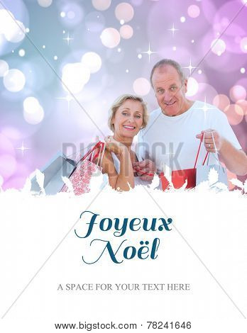 couple with shopping bags against joyeux noel