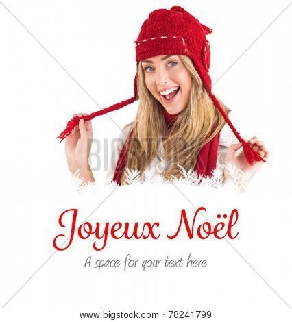Pretty blonde smiling at camera in warm clothes against joyeux noel