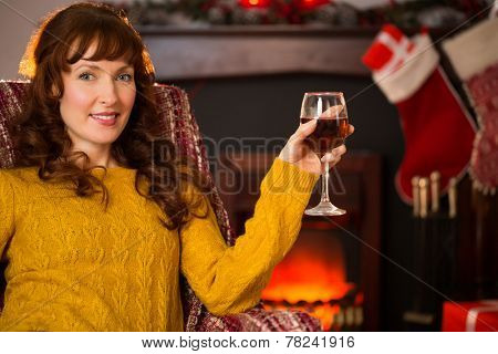 Woman sitting on a couch while holding a glass of red wine at christmas at home in the living room
