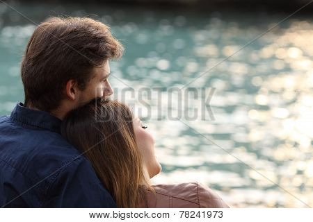 Couple Hugging And Watching The Sea On The Beach