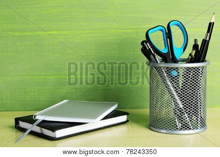 Metal holder with pens, pencil and scissor near the notebooks on wooden table and green wooden background