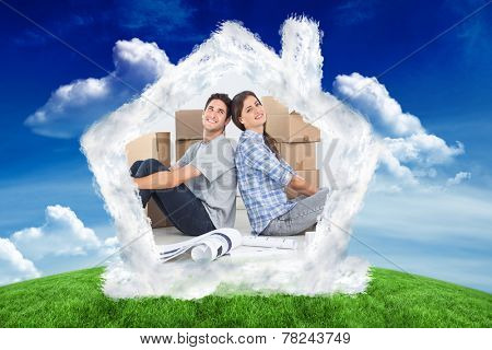 Beautiful couple sitting back-to-back against green field under blue sky