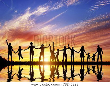 Happy group of diverse people, friends, family, team standing together holding hands and celebrating success. Water reflection, sunset sky