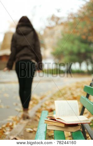 Book left on the bench with silhouette of girl walking away in autumn park
