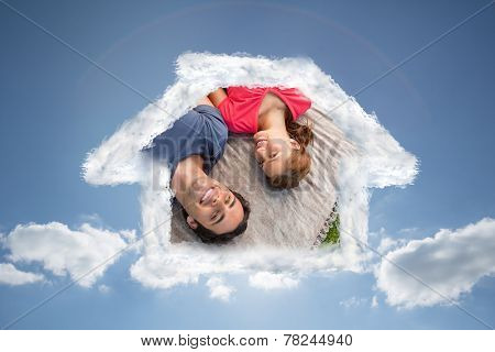 Two friends looking towards the sky while lying on a quilt against cloudy sky with sunshine