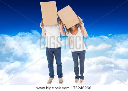 Mature couple wearing boxes over their heads against bright blue sky over clouds