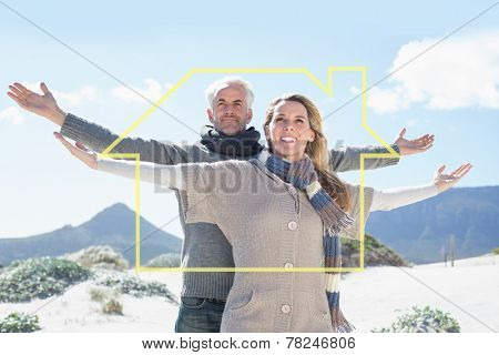 Carefree couple standing on the beach in warm clothing against house outline