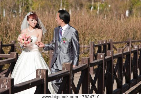 Happy Bride And Groom Walking Over Bridge (1)