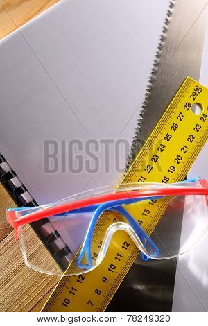 Ruler, Notebook, Handsaw And Goggles