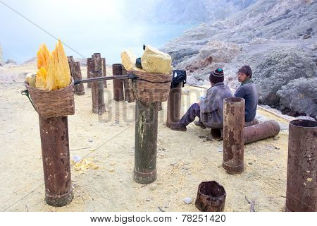 BANYUWANGI, EAST JAVA NOV 12 : Sulphur miners resting before collecting hardened sulphur from ceramic pipes to be sold, Nov 12, 2012, Ijen volcano, East Java, Indonesia.They make only 62cts per kilo.