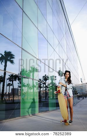 Attractive hipster girl holding longboard standing on beautiful background with reflected palm trees