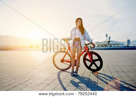 Attractive young woman win fixed gear bike posing outdoors with soft sunset light on background