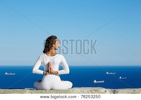 Woman seated in yoga pose on amazing sea background woman meditating yoga enjoying sunny evening