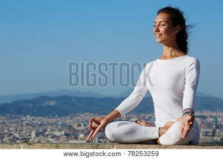 Yoga on high altitude with big city on background smiling woman seated in yoga pose