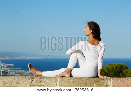 Yoga on high altitude with big city and sea on background, young woman seated in yoga pose