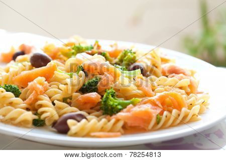 Delicious plate of pasta for lunch consisting of spiral pasta, broccoli, olive, smoke salmon in olive oil.