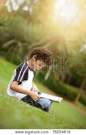 Young pan asian boy enjoying his reading book in outdoor park at sun down