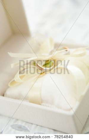 Closeup of diamond wedding ring in a cream colored box with pretty satin ribbon.