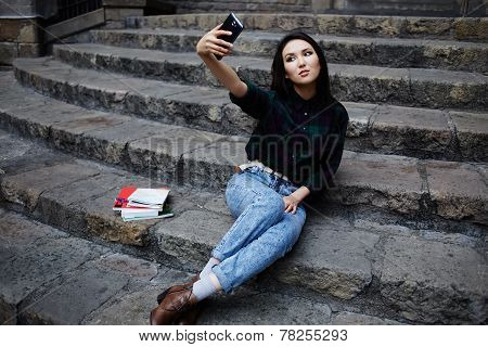Pretty tourist girl taking a self portrait with smart phone in Barcelona