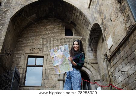Charming tourist woman studying a map standing in gothic quarter in Barcelona