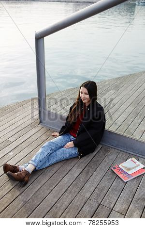 Attractive student girl resting outdoors during her class break in college