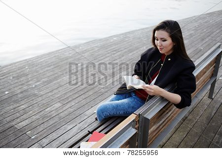 Asian student girl reading book seated on the bench attractive college student reading book