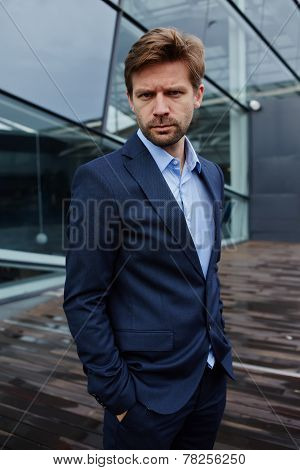 Portrait of sad businessman standing with hands in suit pockets