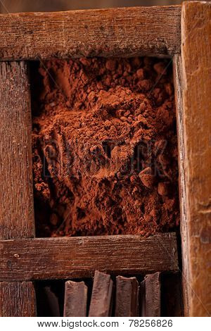 cocoa powder in old spicy box, wooden background