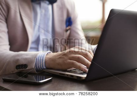 Young businessman typing on laptop