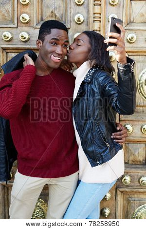 Stylish couple having fun making self portrait picture on digital camera of mobile phone