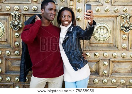 Laughing couple on christmas vacation making self portrait with digital camera on phone