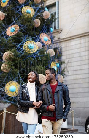 Laughing couple on christmas vacation walking in the city beautiful young couple having fun