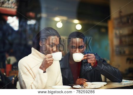 Happy stylish friends having coffee together cold winter days in beautiful coffee shop