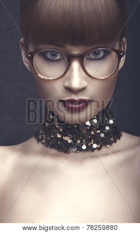 Graceful lady in eyeglases with red lips ,brown forelock and sequin necklace.