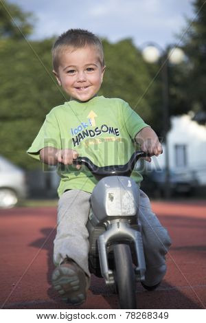 Handsome little boy rides toy motorbike, outdoor