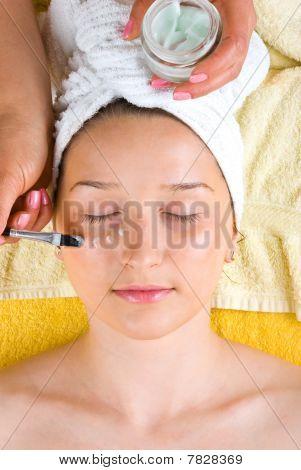 Esteticista aplica crema en el ojo de la mujer
