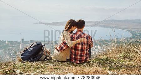 Loving Couple Sitting On Hill Above The City