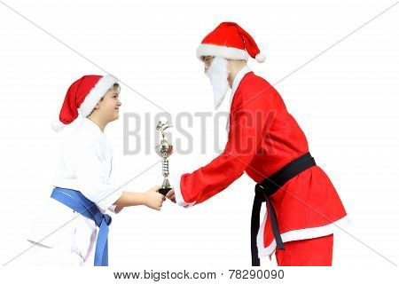 Santa Claus with  black belt gives athlete with a blue belt Sports Cup