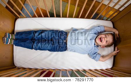 Happy boy lying in a cot with arms and legs stretched